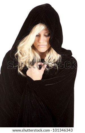 A woman wrapped up in her black cape looking down with a sad expression on her face. - stock photo