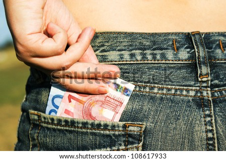 a womanish hand draws out a money from the pocket of jeans - stock photo
