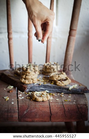 A women decorate chocolate filled cookies made of different healthy flours with seeds and nuts. Dark photo. Selective focus. Also available in horizontal format. - stock photo