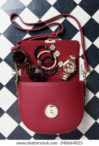 a women elegance bag with accessories get out from her in a black and white background - stock photo