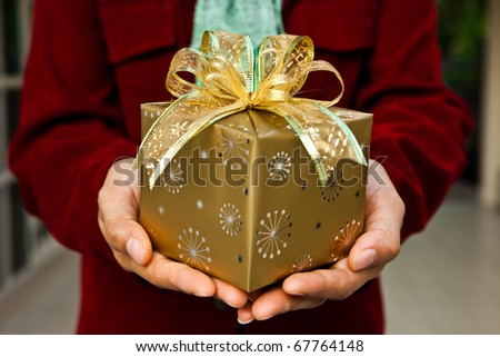 A women hand offering a gift. - stock photo