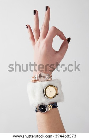 a women hand with the marking of ok and three watches on a studio photo - stock photo