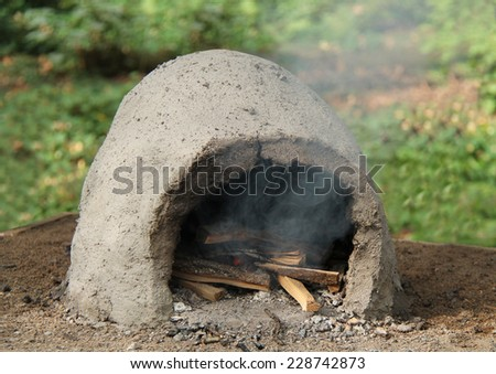 A Wood Burning Fire in an Outdoor Clay Oven. - stock photo