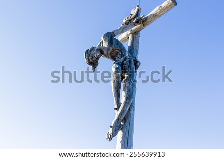A wood carved statue  of the Crucifixion of Jesus Christ on top of the dolomites alps - stock photo
