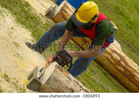 A woodcutter trimming a log with a chainsaw, the sawdust flying. - stock photo