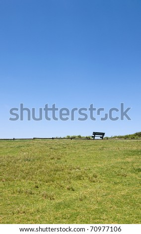 A wooded bench seat on a grassy hill - stock photo