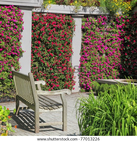 A wooden bench in a colorful garden niche with walls of vibrant flowering impatiens. - stock photo