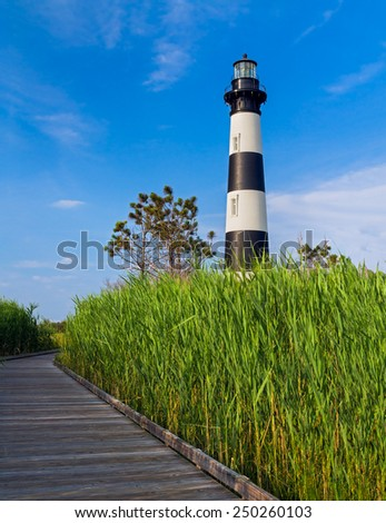 A wooden boardwalk leads through a marsh to the North Carolina's Bodie Island Lighthouse. - stock photo