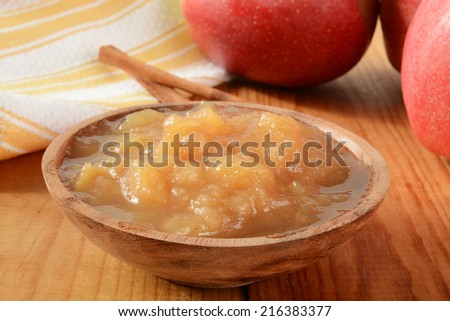 A wooden bowl of fresh applesauce with cinnamon on a rustic wooden table - stock photo