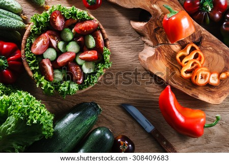 A wooden bowl of fresh vegetable salad surrounded by the ingredients: green lettuce, cucumbers, sweet pepper, tomatoes and  marrows. Top view. - stock photo