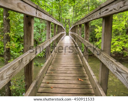 A wooden footbridge on the Appalachian Trail provides safe crossing for hikers over a river - stock photo