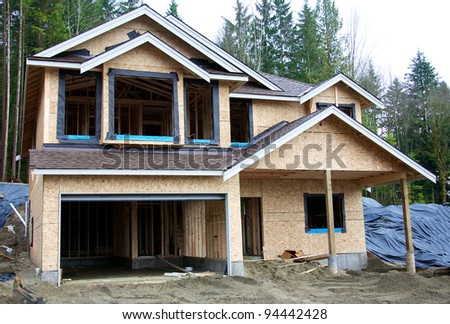 A wooden frame house under construction - stock photo