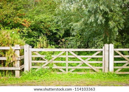 A wooden gate and fence in rural woodland - stock photo