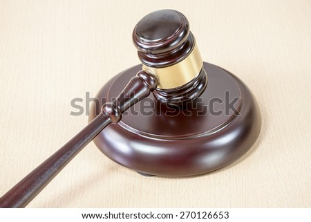 A wooden gavel on wooden table, on brown background - stock photo