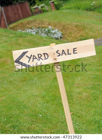 A wooden hand painted yard sale sign outside - stock photo
