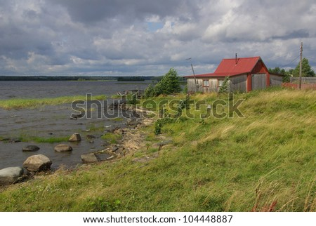A wooden house on the shore of Lake Onega in Karelia, Russia - stock photo
