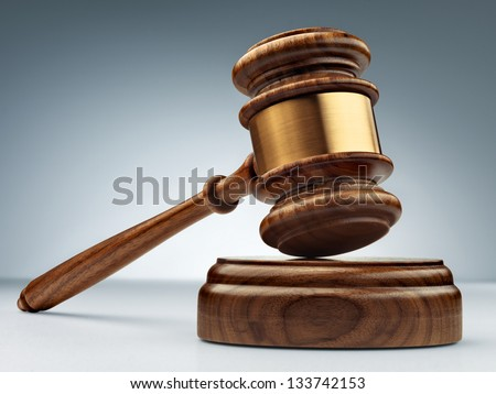 A wooden judge gavel and soundboard on blue  background in perspective - stock photo