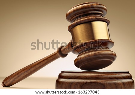 A wooden judge gavel and soundboard on brown background in perspective - stock photo
