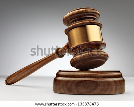 A wooden judge gavel and soundboard on grey - stock photo