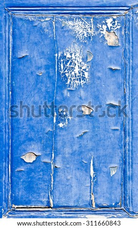 A wooden panel with cracked blue paint - stock photo