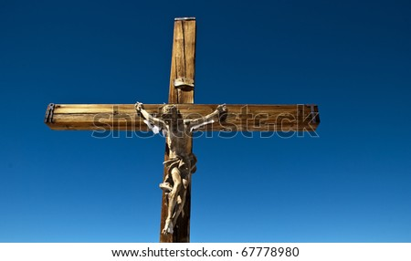 a wooden sculpture of Jesus on the cross with blue sky in the background - stock photo