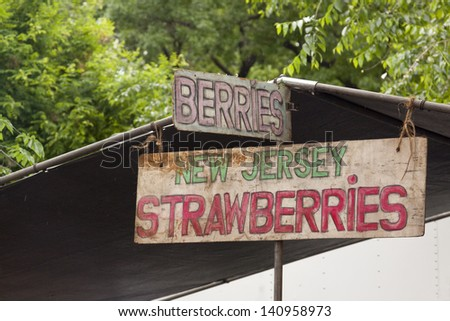 A wooden sign at a farmers market that reads New Jersey Strawberries. - stock photo