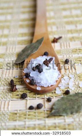 A wooden spoon with coarse sea salt and black pepper on a straw table-bedding, arranged with cloves and bay leaves, closeup, blur background, vertical - stock photo