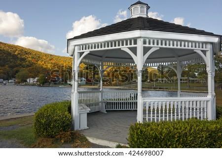 A wooden white gazebo on the lake in Autumn. - stock photo