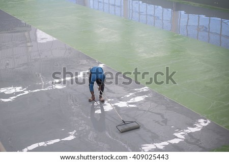 A worker application of epoxy floor - stock photo