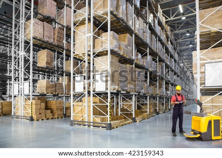 A worker in a huge distribution warehouse with high shelves - stock photo
