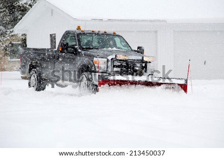a worker plows heavy white snow during a Michigan winter - stock photo