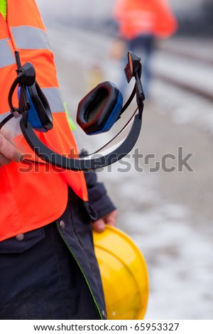 a worker shows his helmet and ear protectors - stock photo
