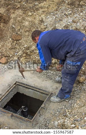 A worker using pick axe to break up conctrete and install new metal frame - stock photo