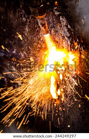 A worker welds a metal structure. Close-up. Burning droplets of metal. - stock photo