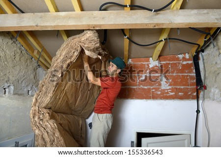 a worker who insert the ceiling insulation - stock photo