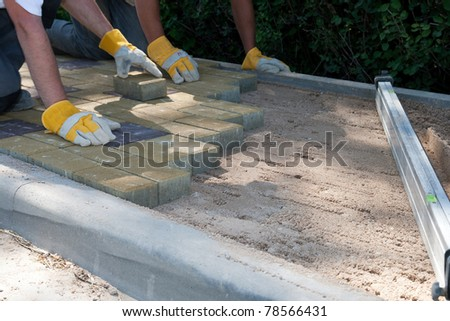 a workers made a sidewalk from bricks - stock photo