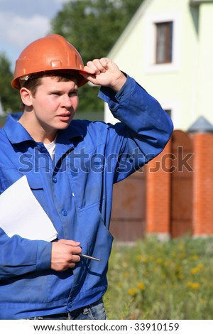 A working man with a plan of construction and keeps his hand helmet - stock photo