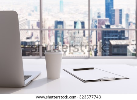 A workplace in a modern panoramic office in Manhattan, New York City. A laptop, notepad and a coffee cup are on the white table. 3D rendering. Toned image. - stock photo