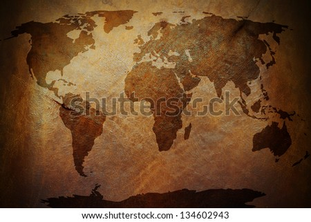 A world map print on an old vintage brown leather parchment. - stock photo