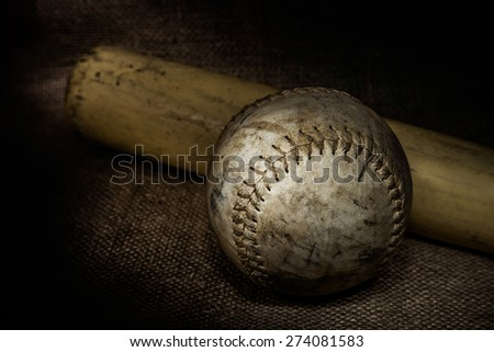 A worn baseball and bat sit atop a burlap surface.  Image was lit using a lightpainting technique. - stock photo