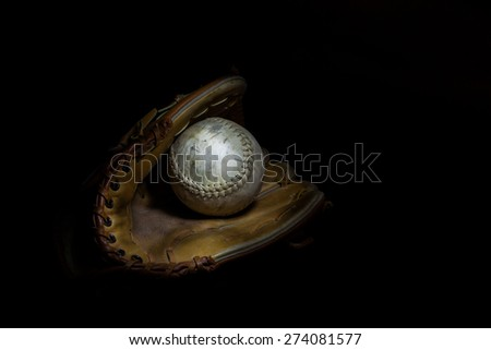 A worn softball sits inside an old baseball glove on a solid black background.  Image was lit by using a lightpainting technique. - stock photo