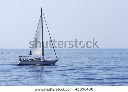 A yacht sailing across an empty sea - stock photo
