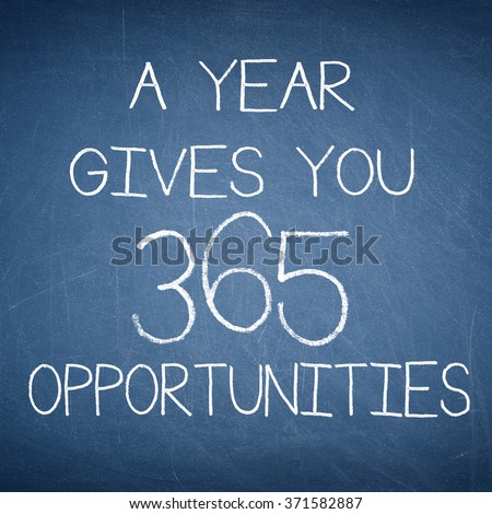 A YEAR GIVES YOU 365 OPPORTUNITIES motivational quote written on a blue blackboard - stock photo