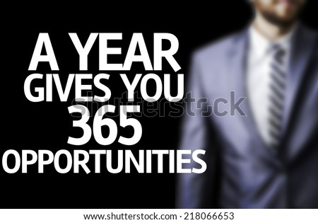 A year Gives You 365 Opportunities written on a board with a business man on background - stock photo
