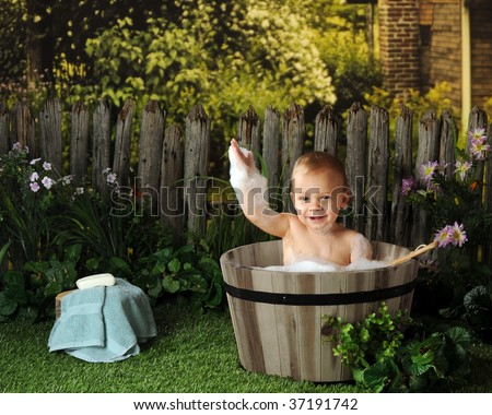 A year-old baby taking an old fashioned bubble bath. - stock photo