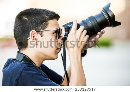 A 12 year old boy about to take a  photograph. - stock photo