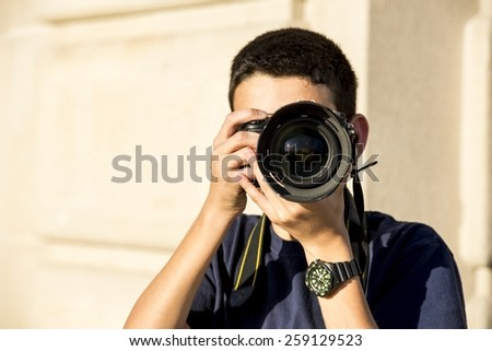 A 12 year old boy about to takea  photograph. - stock photo