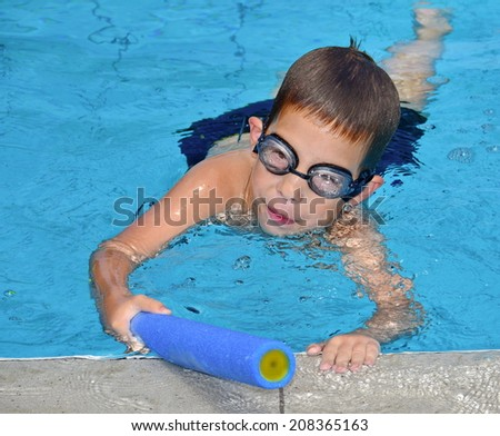 A 6-year-old boy having fun in the swimming pool with a toy water squirt gun - stock photo