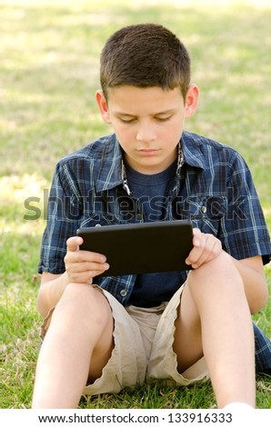 a 10 year old boy in the park with his tablet. - stock photo
