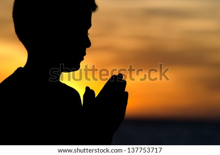 "A 10 year old boy praying at sunset at ""Big Beach"" in Maui. - stock photo"